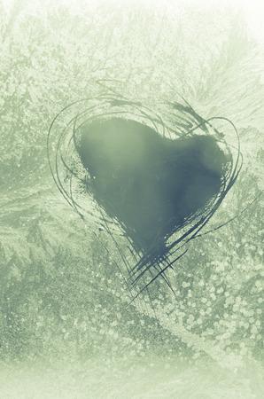 scratched heart shape on frosty pattern on the window