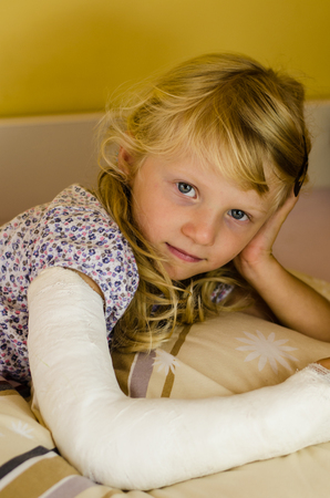 gyps: hurt blond girl with broken hand lying on hand Stock Photo