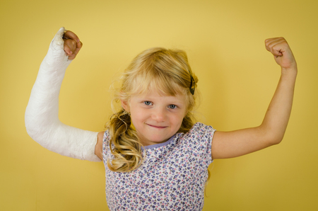 hurt blond girl with broken hand doing sport gesture of strength and triumph Stock Photo