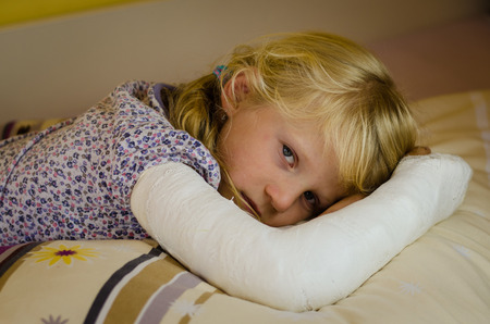 hurt blond girl with broken hand  lying in hand Standard-Bild