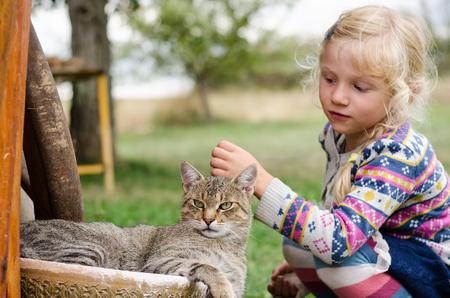 fondling: adorable caucasian blond girl caressing domestic cat Stock Photo