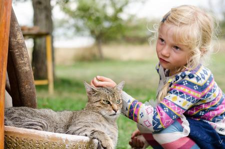 caress: adorable caucasian blond girl caressing domestic cat Stock Photo