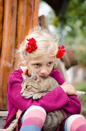 blond girl: adorable caucasian blond girl holding domestic cat