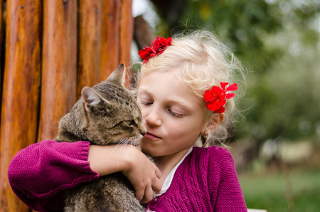 fondle: adorable caucasian blond girl holding domestic cat