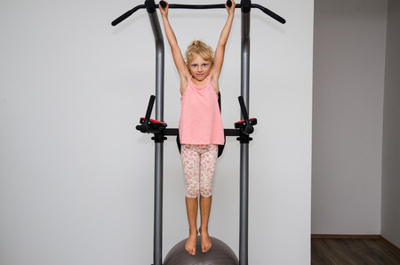 hang body: little blond girl working out in the gym