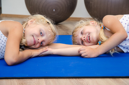 niñas sonriendo: two little blond girls in gym with gray fit balls and blue matts doing exercise