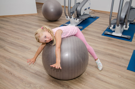 fit ball: little blond girl feeling happy exercising with gray fit ball in the gym