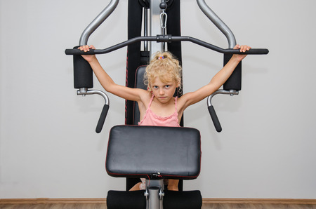 hang body: adorable little blond girl working out in the equipment in the gym