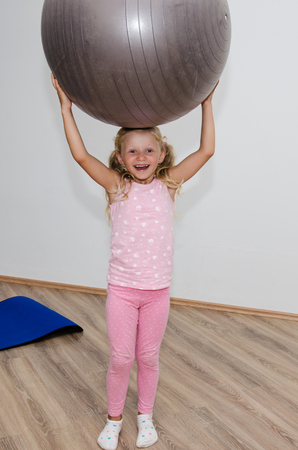fit ball: little blond girl holding gray fit ball over her head