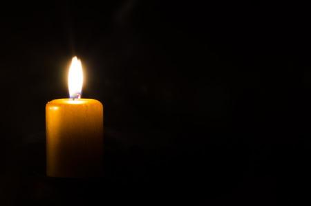 one burning candle decoration against black background