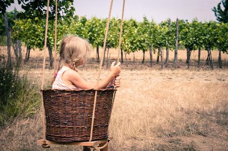 wicket: little blond girl spinning in wicket basket Stock Photo