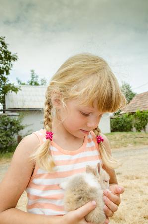 niños rubios: chica rubia que sostiene el pequeño conejo de conejito