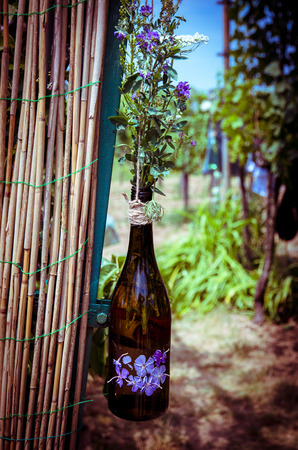 glass fence: flowers in glass bottle hanged over wooden fence