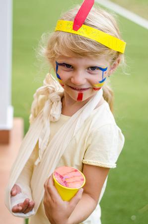 maquillaje infantil: niña rubia con colorido diadema y un vendaje en la pintura de la mano y la cara Foto de archivo