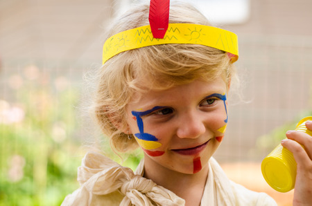 blond girl: smiling little blond girl with Indian facepainting