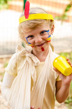 face painting: little blond girl with colorful headband and bandage on hand and face painting