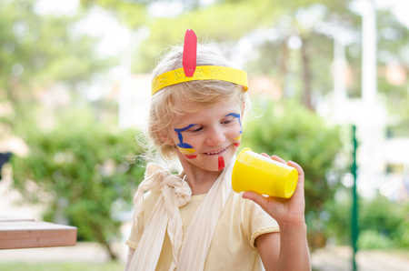 cute girl: little blond girl with colorful headband and bandage on hand and face painting