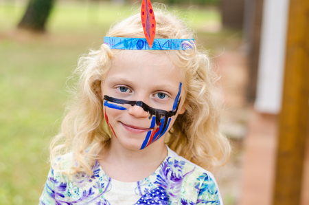 facial painting: little blond girl with abstract facepainting