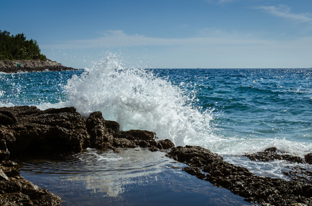 splash of water: huge water splash on rocky coast and blue sea Stock Photo