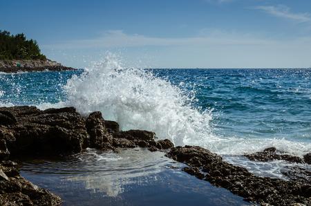 huge water splash on rocky coast and blue sea Standard-Bild
