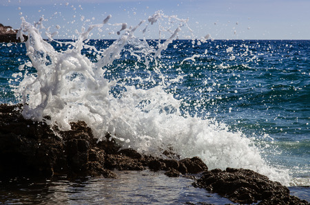 grote golven op de rotsachtige kust en blauwe zee