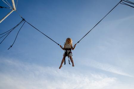 attraction: little courageous kid jumping in bungee attraction