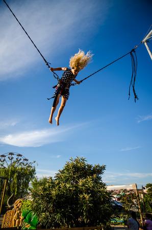 bungee jumping: niña con el pelo largo y rubio dando vueltas en la atracción de bungee