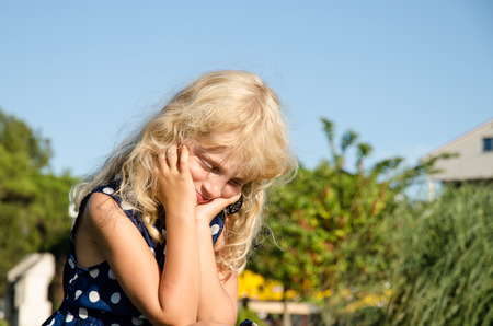 blonde little girl: little blond girl in thinking posture holding her head with hands