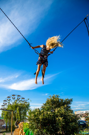 attraction: little child jumping in bungee attraction