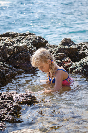 swimm: little blond girl sitting in the sea water protected by the rocks Stock Photo
