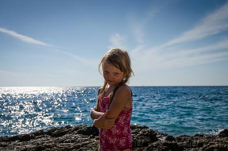 portrait of girl: little blond girl portrait behing blue sea horizon, rocks and blue sky