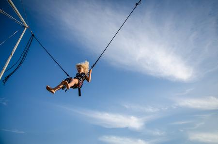 bungee jumping: niña con el pelo largo y rubio que sopla en el aire saltando en la atracción de bungee