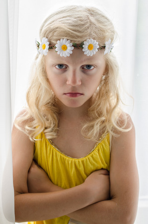 dissapointed: angry blond girl with daisy flower headband with crosses hands Stock Photo