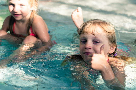 little  blond girls swimming in the swimming pool