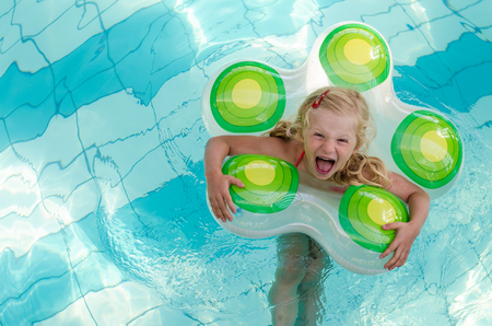 kids playing water: adorable laughing blond girl in inflatable ring in the swimming pool Stock Photo
