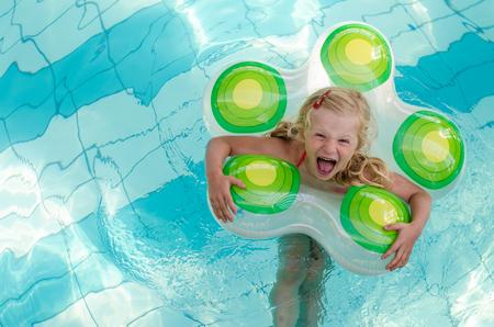 natacion niños: adorable niña rubia riendo en el anillo inflable en la piscina