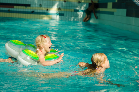 girl with rings: two little blond girls swimming in indoor swimming pool Stock Photo