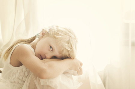 innocent: beautiful blond girl sitting by the curtain desaturated portrait Stock Photo