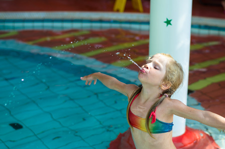 wetsuit: little blond girl in swimsuit and inflatable ring spitting water in the swimming pool