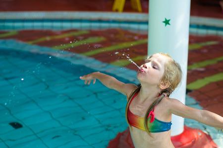 ragazze bionde: poco ragazza bionda in costume da bagno e acqua sputare anello gonfiabile in piscina