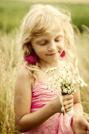 dreamlike: beautiful dreamlike little girl with long blond hair and bunch of flowers in the meadow portrait desaturated effect