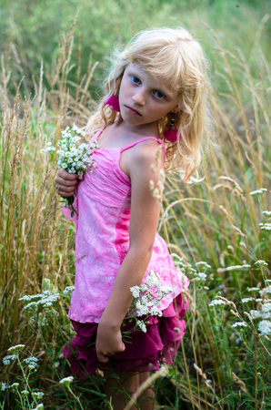 innocent: adorable girl model with long blond hair and bunch of flowers in the meadow