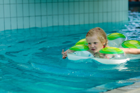 blonde little girl: little  blond girl in inflatable ring swimming in the swimming pool Stock Photo