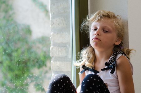dissapointed: bored blond girl sitting alone by the window