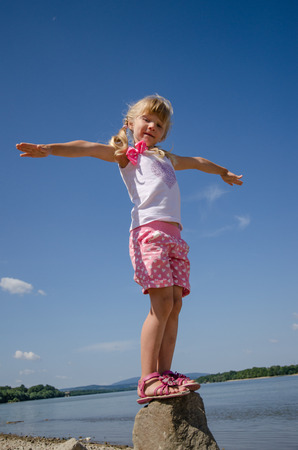 innocent: adorable happy girl standing in the rock by the blue river and blue sky with opened hands