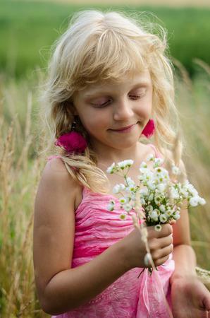 dreamlike: beautiful dreamlike little girl with long blond hair and bunch of flowers in the meadow portrait