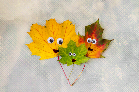 niños de diferentes razas: concepto de familia hecha de hojas de otoño de hojas de color amarillo, verde y naranja Foto de archivo
