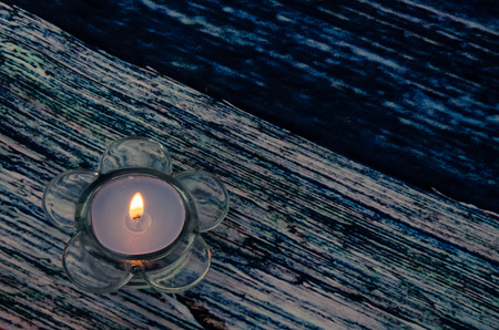 candleholder: burning candle in candleholder with shape of flower against blue wooden background Stock Photo