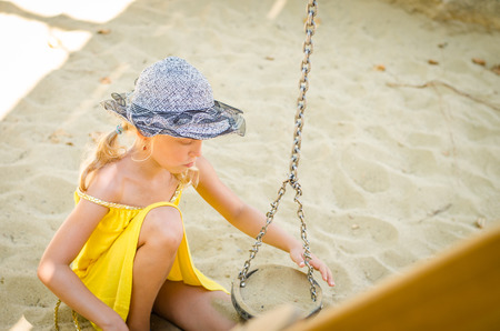 sandpit: little blond girl playing in sandpit on the playground