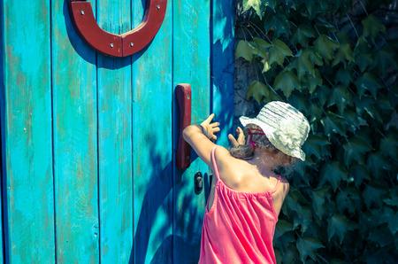 locked door: curious little girl trying to open a wooden locked door